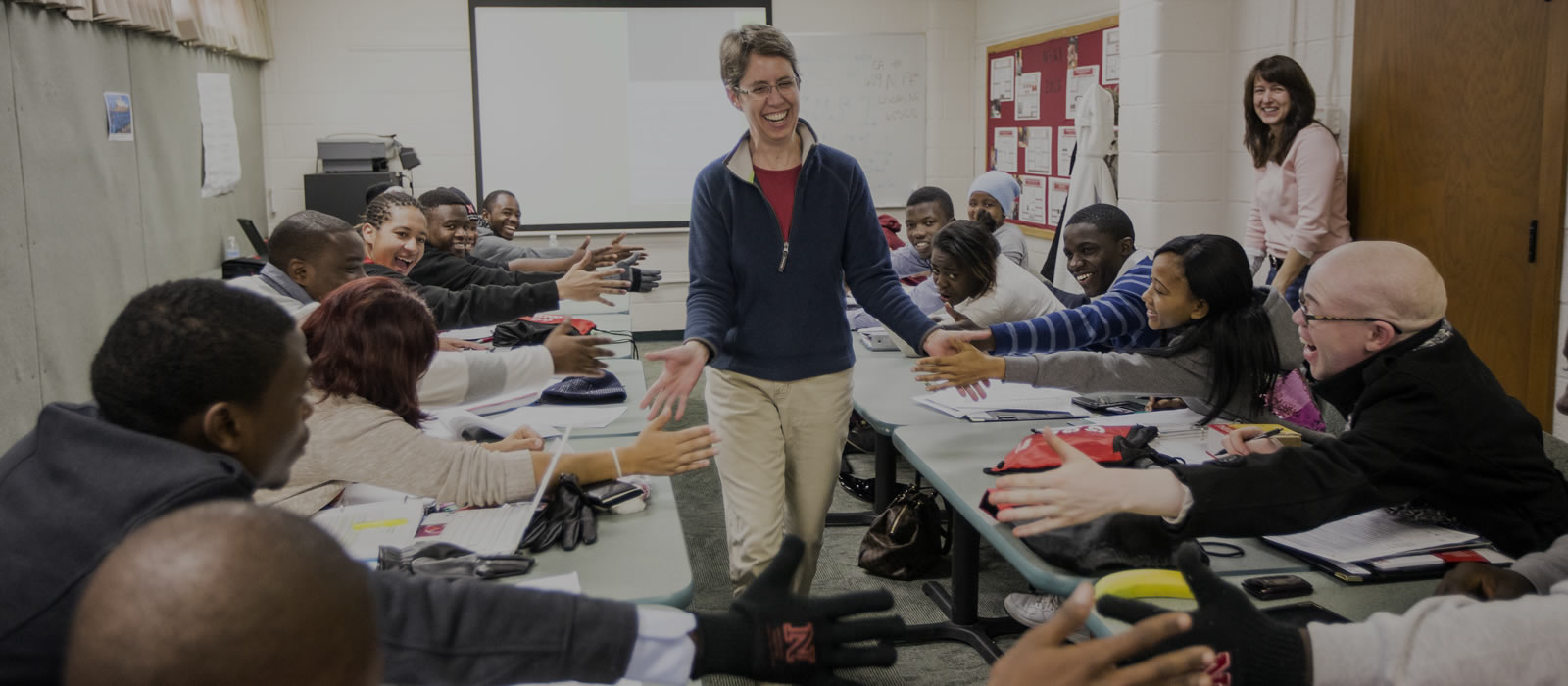 Theiss-Morse giving high fives to students in a classroom